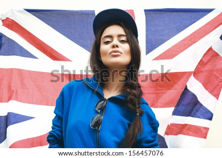 Beautiful young brunette woman in stylish clothes and sunglasses with national british flag in background. Outdoors, Lifestyle - stock photo