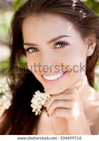 beautiful young brunette woman in the park on a warm summer day - stock photo