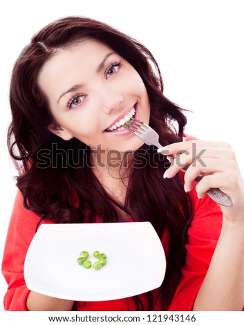 beautiful young brunette woman keeping a diet and eating peas
