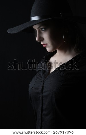beautiful young brunette woman lady posing in a studio on a black background with old style hat - stock photo