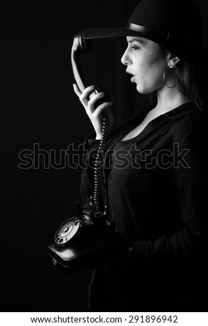 beautiful young brunette woman lady posing in a studio on a black background with old style hat tongue licks old phone  - stock photo