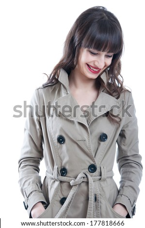 Beautiful young brunette woman model with long curly hair in locks and straight fringe wearing red lipstick and a rain coat, smiling and laughing. Isolated on white background - stock photo