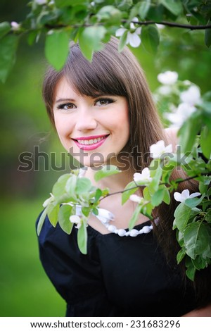 beautiful young brunette woman on the meadow with white flowers on a warm summer day. - stock photo