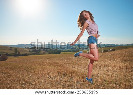 beautiful young brunette woman outdoor on the hill on a summer - stock photo