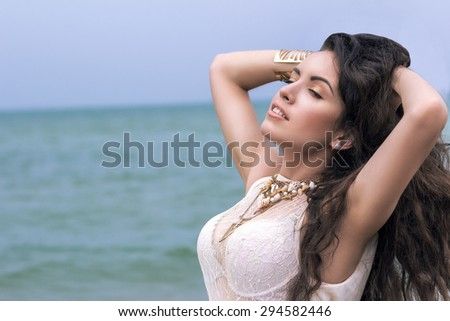 Beautiful young brunette woman outdoors portrait near the sea - stock photo