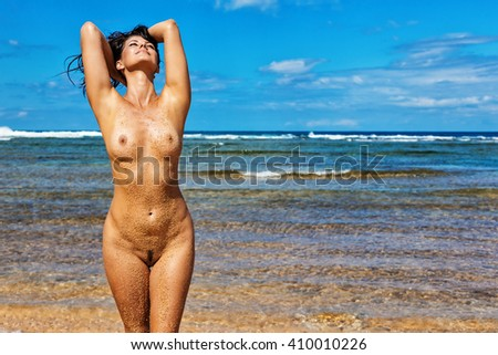 Beautiful young brunette woman posing nude on a remote Hawaiian beach with her hands in her hair, body covered with sand. - stock photo