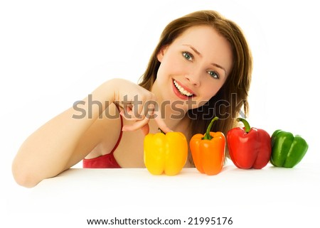 beautiful young brunette woman sitting by the table with colorful peppers - stock photo