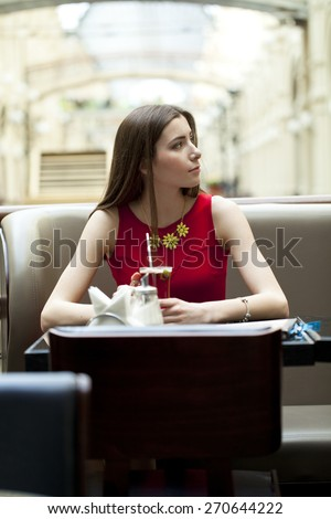 Beautiful young brunette woman sitting in a coffee shop and drink tea - stock photo