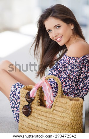 Beautiful young brunette woman sitting on the floor in summer dress with beach bag. Summer time. Portrait outdoor. Portrait of pretty cheerful woman  - stock photo