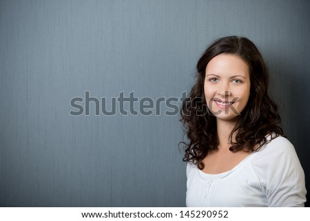 Beautiful young brunette woman standing smiling at the camera against a dark grey background with copyspace - stock photo