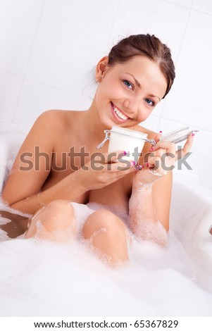 beautiful young brunette woman taking a relaxing bath with foam and applying body scrub