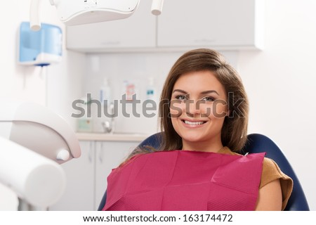Beautiful young brunette woman visiting dentist  - stock photo