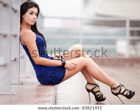 beautiful young brunette woman wearing a blue mini dress in the street - stock photo