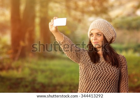 Beautiful young brunette woman wearing brown knitted sweater and beige knitted hat taking a selfie using smartphone. Closeup of happy girl photographing herself outdoors in fall. Medium retouch. - stock photo