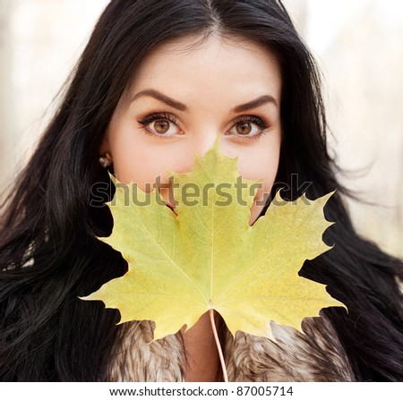 beautiful young brunette woman with a maple leaf  in her hand,  spending time in the autumn park - stock photo