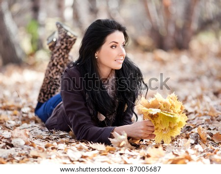 beautiful young brunette woman with maple leaves in her hands,  spending time in the autumn park