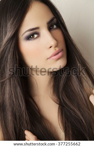 beautiful young brunette woman with perfect skin and nice makeup, studio white