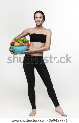 Beautiful young brunette woman with slim body holding bowl with fruits and vegetables. Healthy eating lifestyle and weight loss concept.  White background - stock photo