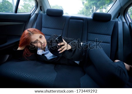 Beautiful young business asian woman using a smart phone in a car - stock photo