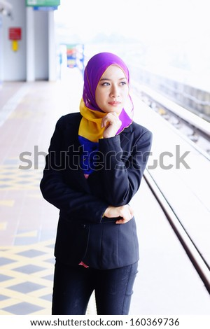 Beautiful young business executive waiting for train - stock photo