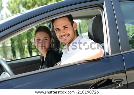 beautiful young business people man and woman driving a rental car for business trip - stock photo