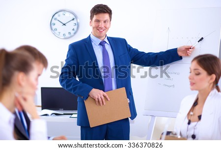 Beautiful young business people with colleagues discussing in the background - stock photo