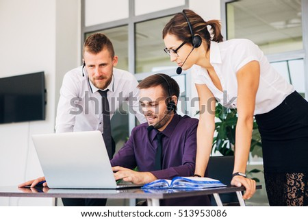 beautiful young business woman and businessmans in headsets using laptops while working in office