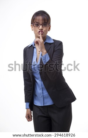 Beautiful young business woman gesturing silence over white background - stock photo
