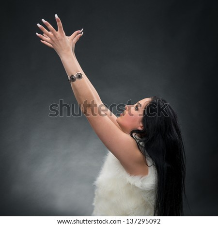 Beautiful young business woman holding her hands up on a gray background - stock photo