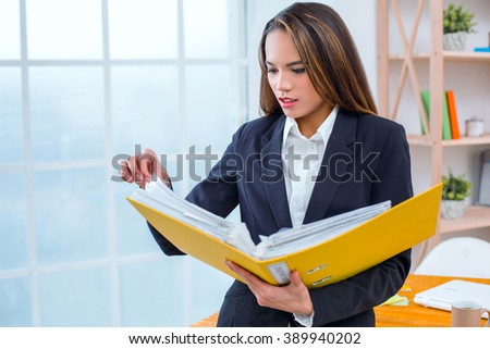 big beautiful modern office photo. beautiful young business woman in modern office with big window holding folder documents photo