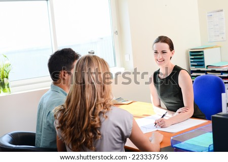 beautiful young business woman in selling transaction with happy young couple in office   - stock photo