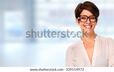 Beautiful young business woman over blue office background. - stock photo