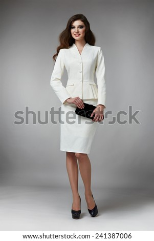 Beautiful young business woman with evening make-up wearing a white business suit skirt to the knee and jacket high heels and a small handbag, business clothes for meetings and walks autumn collection - stock photo