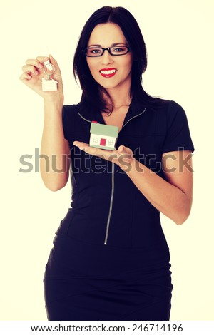 Beautiful young business woman with house construction and keys.  - stock photo