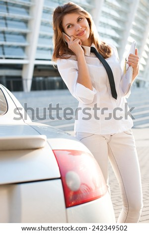 Beautiful young business woman with magazine talking on the phone. City business woman working / talkative woman in a white button down shirt with black tie  - stock photo