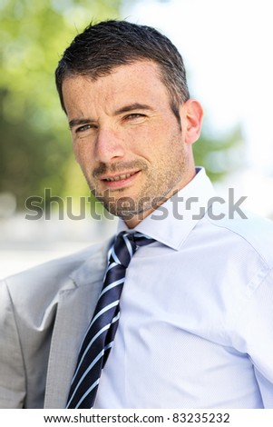 beautiful young businessman with tie outdoor in spring - stock photo