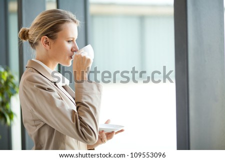 beautiful young businesswoman drinking coffee in office - stock photo