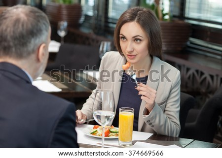 Beautiful young businesswoman has a business lunch with her client in cafe. She is eating salad and listening to businessman attentively - stock photo