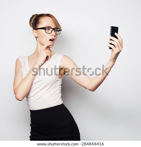 Beautiful young businesswoman holding mobile phone and making photo selfie while standing against grey background - stock photo