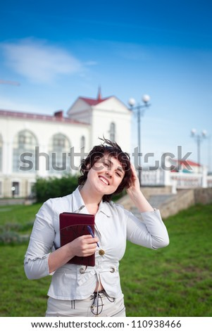 Beautiful young businesswoman holding notebook