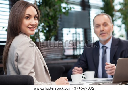 Beautiful young businesswoman is discussing the project with her client in cafe. They are looking at the camera and smiling