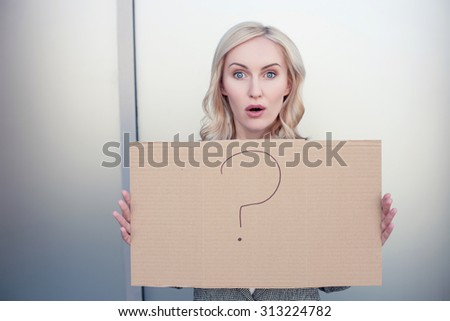 Beautiful young businesswoman is holding a signboard with a question mark on it. She is looking at the camera with frustration. Her mouth and eyes are wide open - stock photo