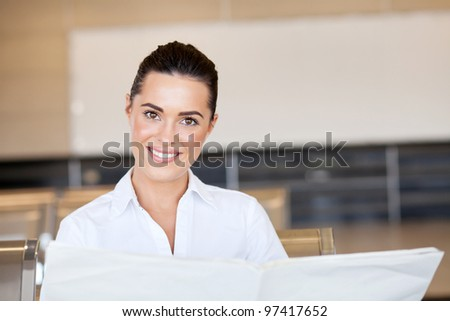 beautiful young businesswoman reading newspaper at airport - stock photo