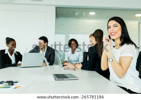 Beautiful young businesswoman receiving good news on the phone with her smile hinting at future fruitful business deals - stock photo