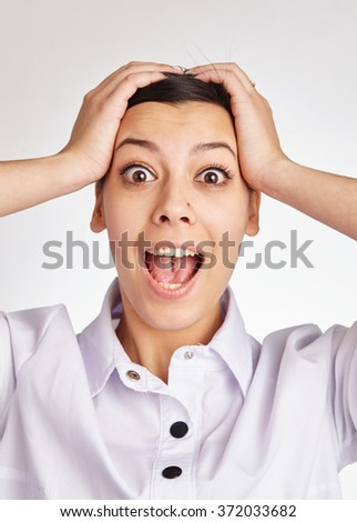 Beautiful young businesswoman screaming and holding head in hands while standing against white background. - stock photo