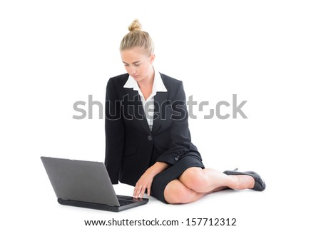 Beautiful young businesswoman sitting on floor using her notebook on white screen