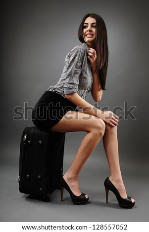Beautiful young businesswoman sitting on the trolley over gray background, traveling concept - stock photo