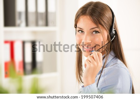 Beautiful young businesswoman talking on headset. Looking at camera. - stock photo