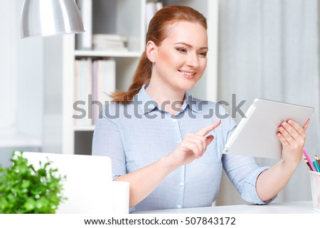 Beautiful young businesswoman working at tablet while sitting on her working place