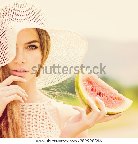 Beautiful young Caucasian blonde woman in beige crochet hat and top posing holding a slice of watermelon. Retouched, filter applied, square format. - stock photo